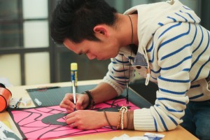 Designstudent benutzt die Scherenschnitttechnik