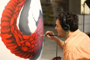 Designstudent Juan malt ein Dino auf das Ei drauf