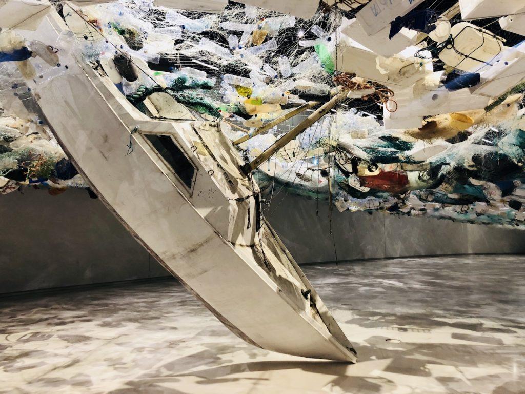 Designstudentin unter einem Meer aus Plastikmüll